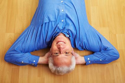 Älterer Mann liegt entspannt auf Parkettboden